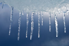 Beautiful icicles against the storm sky Royalty Free Stock Photos