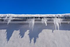 Beautiful icicles Shine in the sun against the blue sky. Spring landscape with icicles hanging from the roof. Winter scene with royalty free stock images