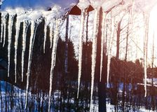 Beautiful icicles shine in sun against blue sky. spring landscape with ice icicles hanging from roof of house. Spring drops icicle. S dripping. Melting snow stock image