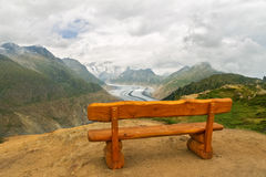 Beautiful idyllic Alps landscape with wooden bench on viewpoint, mountains in Switzerland Royalty Free Stock Images