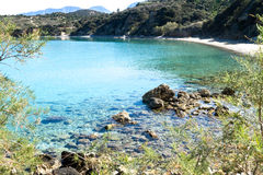 Beautiful idyllic turquoise waters coast with pebbles and rocks. Royalty Free Stock Images