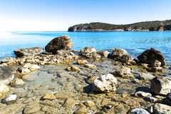 Beautiful idyllic turquoise waters coast with pebbles and rocks. Stock Photos