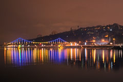 Beautiful illumination of Pedestrian Bridge reflected in the water. Evening view on the promenade along the Dnieper stock images