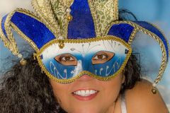 Image of the face of a smiling woman with black curly hair wearing a Venetian mask stock photos