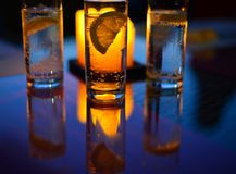 A beautiful image of a glass with mineral sparkling water and a slice of lemon inside. On the luminaire of a candle with an orange glare and air bubbles on the Stock Photography