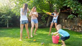 Beautiful image of happy laughing family with children having fun at hot summer day with water guns and garden hose. Beautiful photo of happy laughing family stock photography