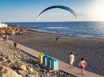 Beautiful image of male paraglider landing on the ocean beach