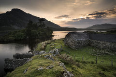 Beautiful image of stone barn with mountains and lake at sunrise Stock Photos