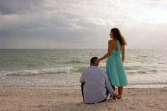 Beautiful image of two young lovers at the beach a. Beautiful romantic image of young couple holding each other  at the beach in the gulf of mexico looking out Royalty Free Stock Images