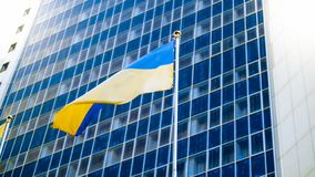 Beautiful image of Ukrainian flag fluttering on wind against high modern office building. Beautiful photo of Ukrainian flag fluttering on wind against high royalty free stock photography