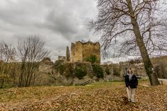 Beautiful image of a woman with her dog enjoying a cold autumn day in front of the ruined Franchimont castle royalty free stock photography