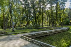 Beautiful image of a wooden walkway zigzag in the park on a sunny autumn day stock photography