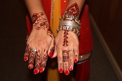 Young bride`s hands with henna tattoos and bracelets, Pakistani wedding celebration, 2016. Beautiful image of young bride`s hands showcasing henna tattoos and stock photo