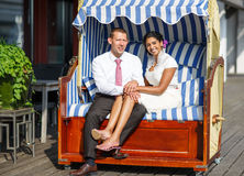 Beautiful indian bride and caucasian groom, in beach chair. Royalty Free Stock Images