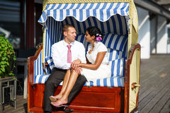 Beautiful indian bride and caucasian groom, in beach chair. Royalty Free Stock Photography