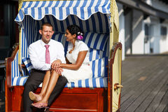 Beautiful indian bride and caucasian groom, in beach chair. Royalty Free Stock Photo