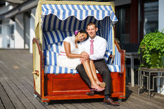 Beautiful indian bride and caucasian groom, in beach chair. Beautiful indian bride and caucasian groom, in beach chair Stock Photography