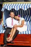 Beautiful indian bride and caucasian groom, in beach chair. Royalty Free Stock Image