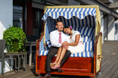 Beautiful indian bride and caucasian groom in beach chair Stock Photos
