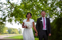 Beautiful indian bride and caucasian groom in park. BeBeautiful indian bride and caucasian groom, in summer park Royalty Free Stock Photos