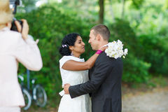 Beautiful indian bride and caucasian groom in park. Beautiful indian bride and caucasian groom in summer park Royalty Free Stock Photography