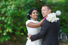 Beautiful indian bride and caucasian groom in park. Beautiful indian bride and caucasian groom in summer park Stock Image