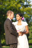 Beautiful indian bride and caucasian groom in park. Beautiful indian bride and caucasian groom in summer park Stock Images