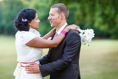 Beautiful indian bride and caucasian groom, in summer park. Beautiful indian bride and caucasian groom, in summer park Stock Image
