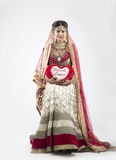 Beautiful Indian Bride on gray background. Beautiful Indian Bride in lehenga on gray background with a heart in her hands Royalty Free Stock Photography