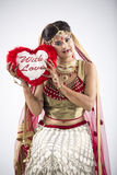 Beautiful Indian Bride on gray background. Beautiful Indian Bride in lehenga on gray background with a heart in her hands Stock Photos