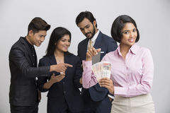 Beautiful Indian businesswoman holding rupees with her busy colleagues Royalty Free Stock Photo