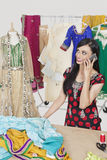 Beautiful Indian female dressmaker answering phone call while standing at table Royalty Free Stock Photo