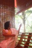 Beautiful Indian Girl Raising Bamboo Curtain Royalty Free Stock Image