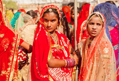 Beautiful indian girls posing serious in colorful crowd Royalty Free Stock Photos