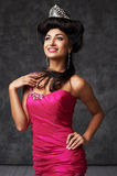 Beautiful indian lady in pink dress and diadem. Black haired indian woman in shiny diadem and pink dress. She has beautiful hairstyle. She wears earrings and Royalty Free Stock Photos