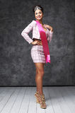 Beautiful indian lady in pink skirt and jacket with shiny diadem and pink ribbon. Pretty indian woman with stylish hairstyle. She has black hair and shiny crown Stock Photo