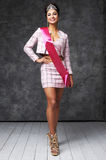 Beautiful indian lady in pink skirt and jacket with shiny diadem and pink ribbon. Pretty indian woman with stylish hairstyle. She has black hair and shiny crown Royalty Free Stock Photo