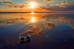 Beautiful Indian ocean sunset. Sunglasses on the Indian ocean sunset beach, Bali island, Indonesia Stock Photography