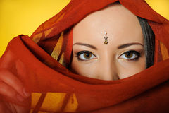 Beautiful indian traditional woman eyes. Young beautiful woman eyes in indian traditional jewellary, bindi , sari dress and makeup. yellow background Royalty Free Stock Photo