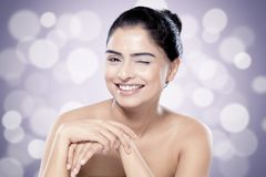 Beautiful Indian woman with healthy skin against blurred lights background. Asian beauty and skincare concept. Beautiful Indian woman with healthy skin winks Royalty Free Stock Photography