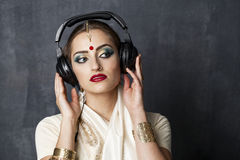 Beautiful Indian woman listening to music on headphones Stock Image
