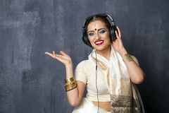 Beautiful Indian woman listening to music on headphones Stock Photos