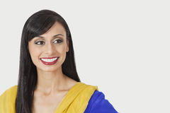Beautiful Indian woman looking sideways over gray background Stock Photography