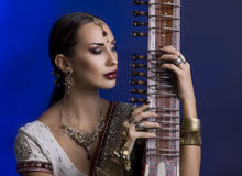 Beautiful Indian Woman in Sari with Oriental Jewelry Playing the Stock Images