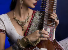 Beautiful Indian Woman in Sari with Oriental Jewelry Playing the Royalty Free Stock Photo