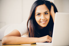 Beautiful Indian woman student using laptop computer at home Royalty Free Stock Photos