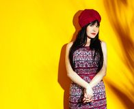 Woman portrait yellow studio background indian shadow sun light turban red. Beautiful indian woman on yellow studio background with shadow and sun light. Young royalty free stock photo