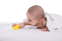 Beautiful infant playing with small yellow duck after shower, is Royalty Free Stock Photo