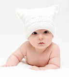 Baby in white hat lies on bed Stock Photography