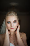 Beautiful innocent blonde bride with blue eyes posing, face clos Stock Photos